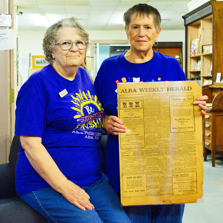 Librarian Cheryl Gill and volunteer Saundra Burge show off an old Alba Weekly Herald from the library/museum's collection.