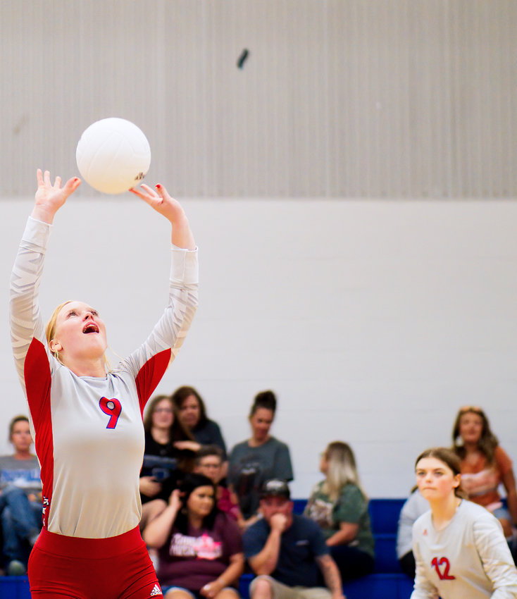 Kaylee Anglin sets the ball as Alexis Wilmut anticipates going to the ball for a kill.