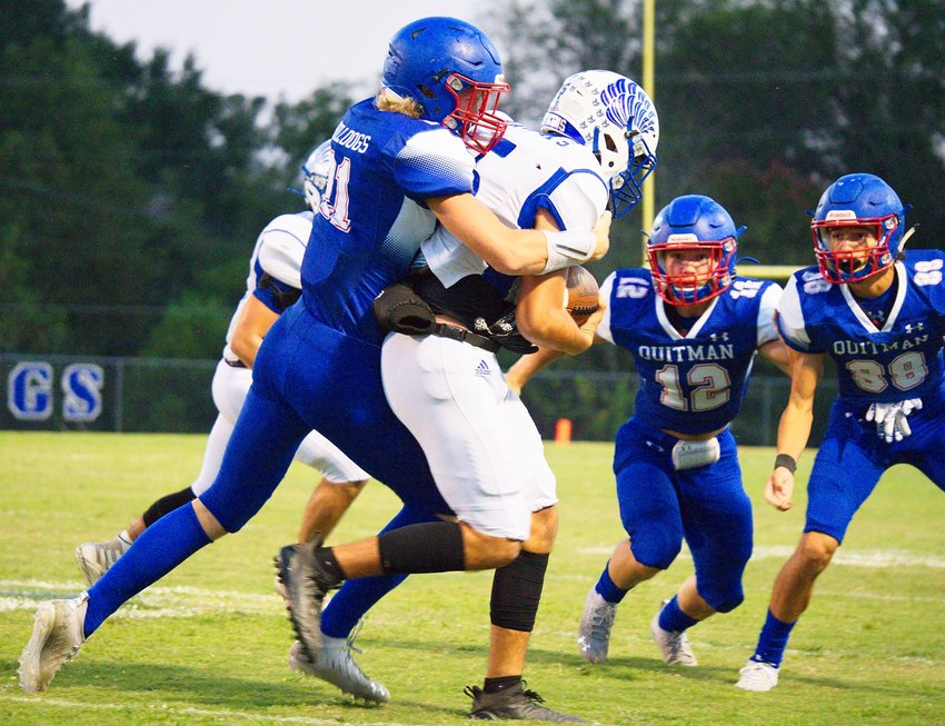 Carson Johnson wraps up the Hawks ball-carrier as Wyatt Hightower (12) and Thomas Sabedra (88) prepare to assist with the tackle.