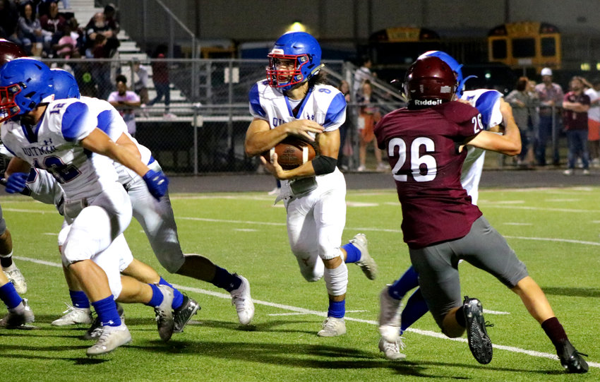 Quitman's Mason Reynolds (8) looks for room to run against Arp Friday night. See story Page 8A.