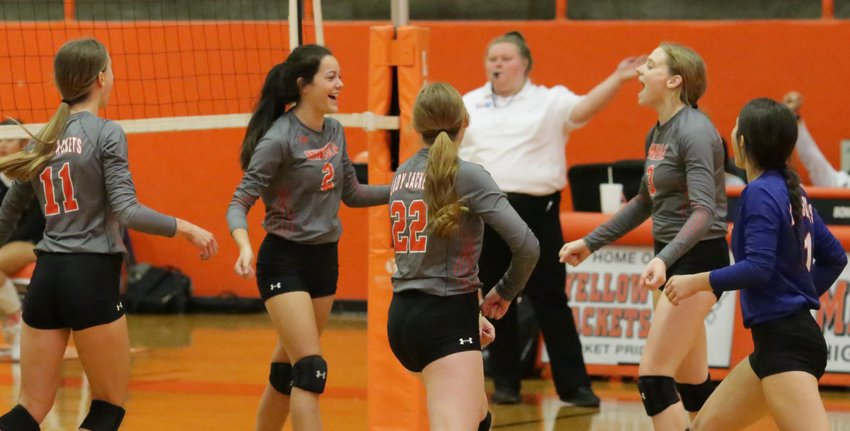 Lady Jackets rush to congratulate Kozbie Riley on her match-winning kill shot against Chapel Hill.