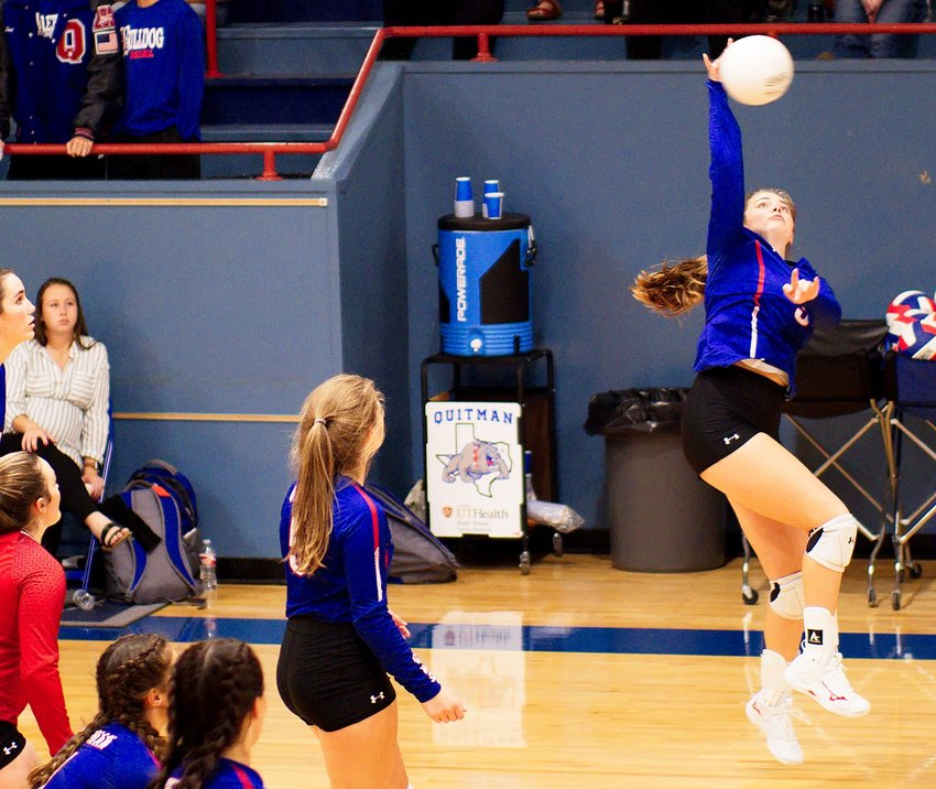 Kaysi Parker spikes the ball for Quitman as her teammates watch.